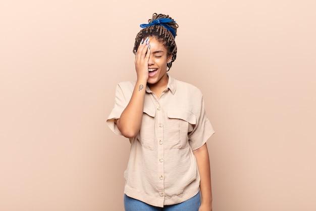 笑って額を叩く若いアフロ女性