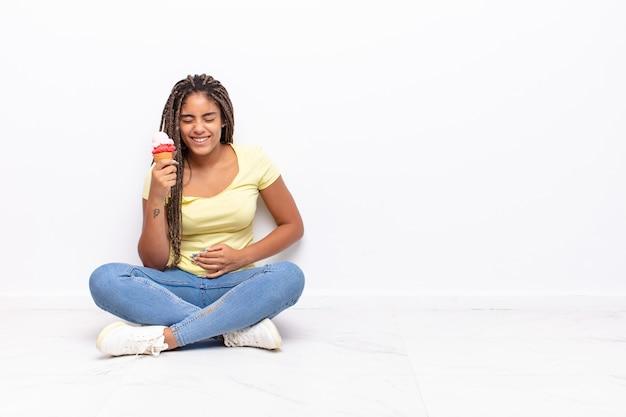 いくつかの陽気な冗談で大声で笑い、幸せで陽気に感じ、楽しんでいる若いアフロ女性。アイスクリームのコンセプト