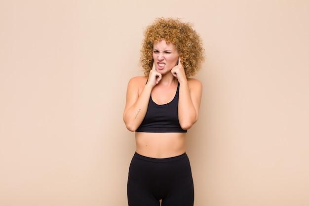 怒っている、ストレス、イライラを探して、耳が聞こえないノイズ、サウンド、または大音量の音楽スポーツコンセプトに両耳をカバーしている若いアフロ女性
