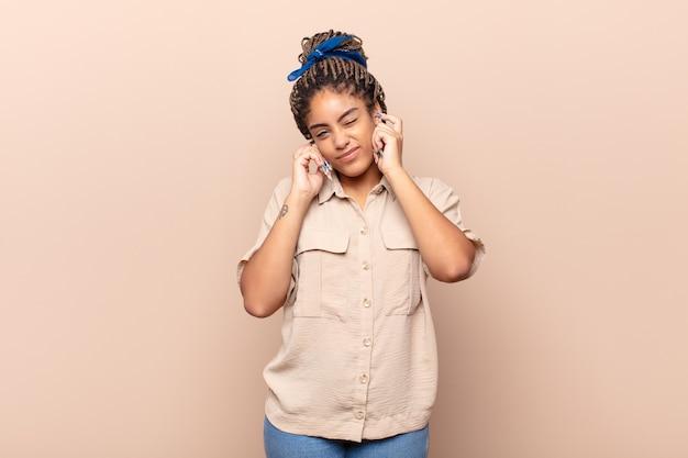 怒り、ストレス、イライラしているように見える若いアフロ女性は、耳をつんざくような音、音、または大音量の音楽で両耳を覆っています