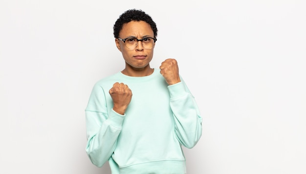 Young afro woman looking confident, angry, strong and aggressive, with fists ready to fight in boxing position
