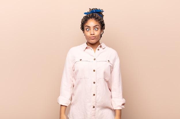 愚かな斜視の表情で間抜けで面白い顔をしている若いアフロ女性