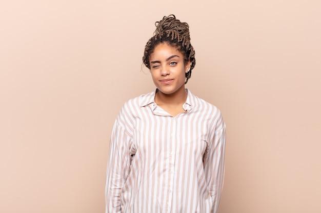 幸せでフレンドリーに見え、笑顔で前向きな姿勢であなたに目をまばたきする若いアフロ女性