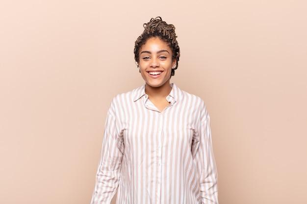 広く、楽しく、ルーニーな笑顔と目を大きく開いて幸せで間抜けに見える若いアフロ女性