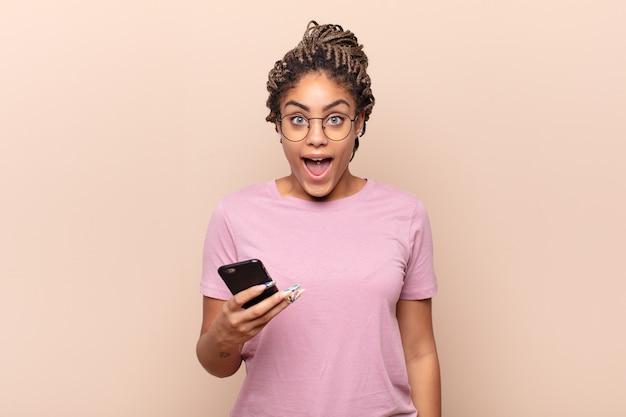 若いアフロの女性は幸せそうにうれしそうに驚き、魅了されてショックを受けた表情で興奮している