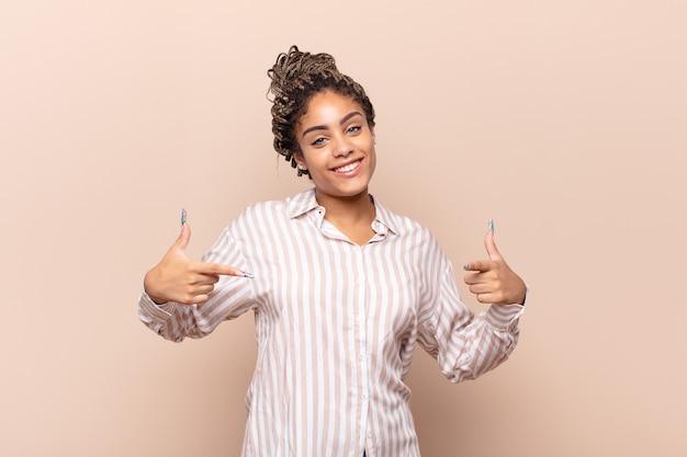 誇らしげに、傲慢で、幸せで、驚き、満足しているように見え、自己を指し、勝者のように感じている若いアフロ女性