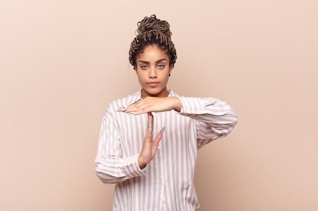 Молодая афро-женщина выглядит серьезной, суровой, сердитой и недовольной, делая знак тайм-аута