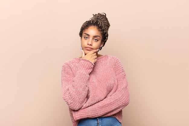 Молодая афро-женщина выглядит серьезной, задумчивой и недоверчивой, скрестив одну руку и положив руку на подбородок, варианты взвешивания