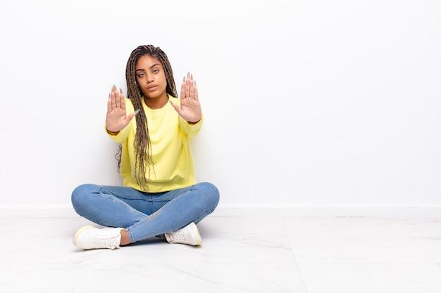 真面目で、不幸で、怒って、不機嫌そうに見える若いアフロの女性は、立ち入りを禁じているか、両方の手のひらを開いて停止すると言っています