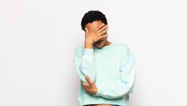 ストレス、恥ずかしがり屋、または動揺して、頭痛で顔を覆っている若いアフロ女性