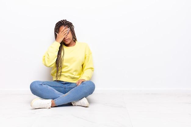 Молодая афро-женщина выглядит напряженной, пристыженной или расстроенной, с головной болью
