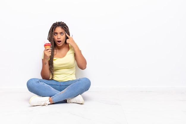 驚いた、口を開いた、ショックを受けた、新しい考え、アイデア、または概念を実現している若いアフロ女性。アイスクリームのコンセプト