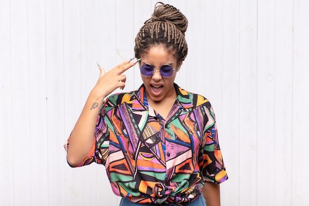 不幸でストレスを感じている若いアフロ女性、手で銃のサインを作る自殺ジェスチャー、頭を指して