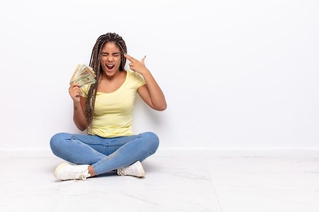 不幸でストレスを感じている若いアフロ女性、自殺ジェスチャー