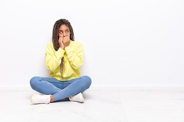 걱정, 불안, 스트레스와 두려워, 손톱을 물고 측면 복사 공간을 찾고 젊은 아프리카 여성