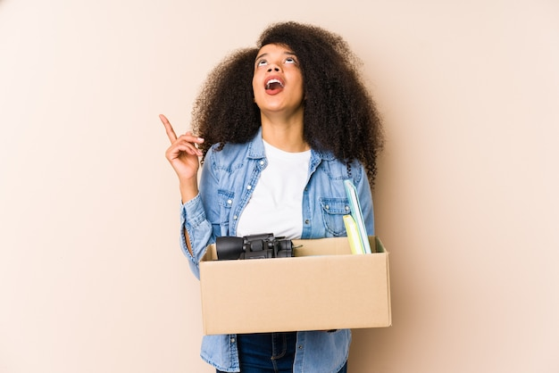Young afro woman moving home isolated young afro woman pointing upside with opened mouth.