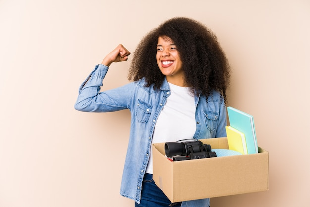 Young afro woman moving home young afro woman raising fist after a victory