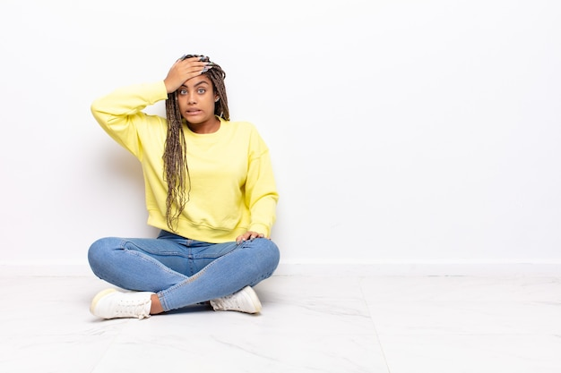 忘れられた締め切りに慌てて、ストレスを感じ、混乱や間違いを隠蔽しなければならない若いアフロ女性