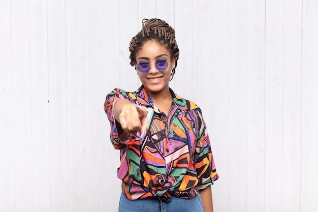 満足、自信を持って、フレンドリーな笑顔でカメラを指して、あなたを選ぶ若いアフロ女性