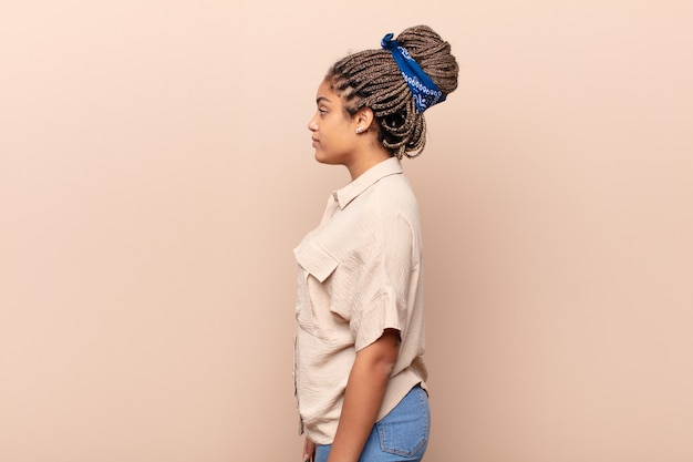 Young afro woman on profile view looking to copy space ahead, thinking, imagining or daydreaming