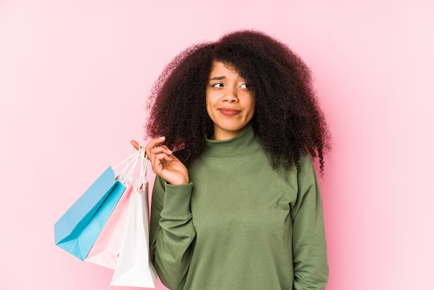 Young afro woman shopping isolated young afro woman buying isolayoung afro woman holding a roses isolated confused, feels doubtful and unsure.< mixto >