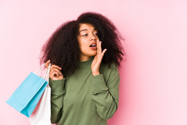 Young afro woman shopping isolated young afro woman buying isolayoung afro woman holding a roses isolated is saying a secret hot braking news and looking aside< mixto >