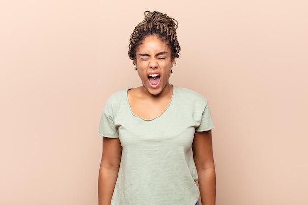 Молодая афро-женщина агрессивно кричит, выглядит очень сердитой, расстроенной, возмущенной или раздраженной, кричит нет