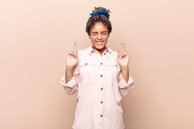 若いアフロの女性は笑顔で心配そうに両指を交差させ、心配を感じ、幸運を願ったり期待したりします
