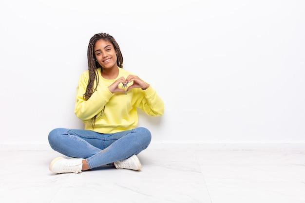 Молодая афро женщина улыбается и чувствует себя счастливой, милой, романтичной и влюбленной изолированной