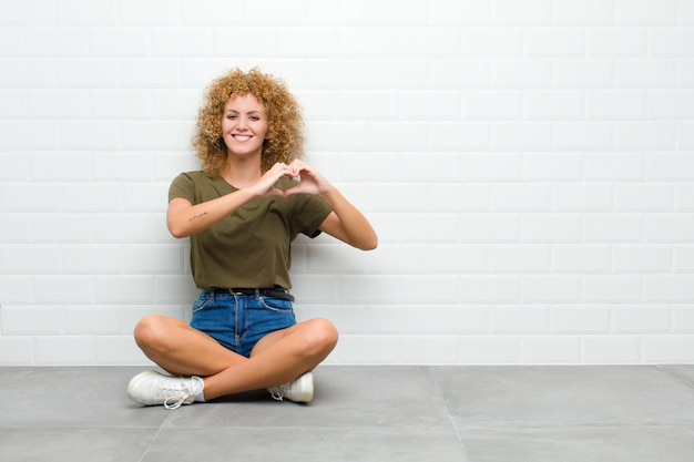 젊은 아프리카 여자 웃 고 행복, 귀여운, 로맨틱 하 고 사랑에 느낌, 양손으로 바닥에 앉아 심장 모양 만들기