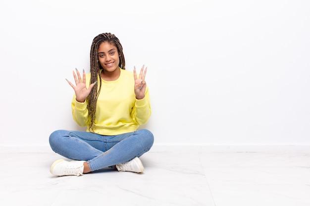 笑顔でフレンドリーに見える若いアフロ女性、前に手を前に8番または8番を示し、カウントダウン