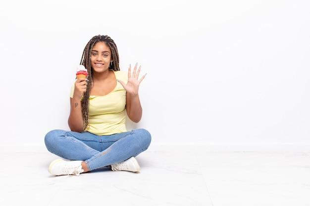 若いアフロの女性は笑顔でフレンドリーに見え、前に手を出して5番または5番を示し、カウントダウンします。アイスクリームのコンセプト