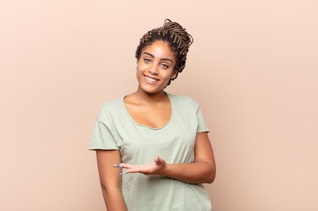 陽気な笑顔、幸せを感じ、手のひらでコピースペースでコンセプトを示す若いアフロ女性