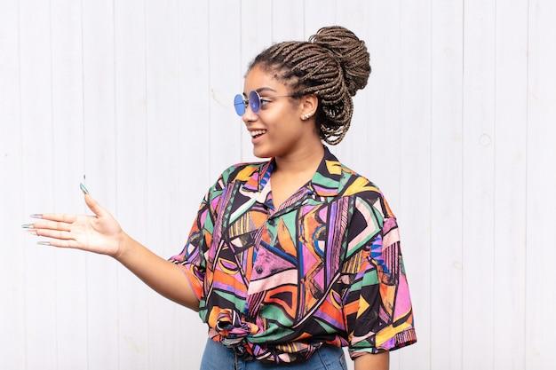 笑顔、挨拶、握手を提供して成功した取引を成立させる若いアフロ女性、協力コンセプト