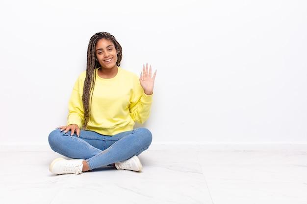 幸せで元気に笑って、手を振って、あなたを歓迎して挨拶するか、さようならを言う若いアフロ女性