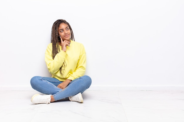 幸せに笑って、空想にふけったり、疑ったり、横を向いている若いアフロ女性