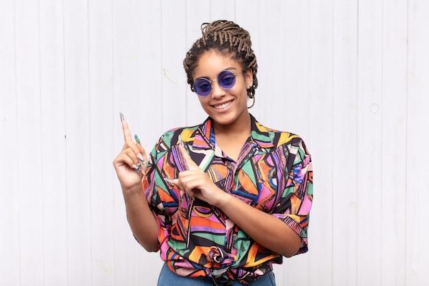 幸せに笑って、コピースペースでオブジェクトを示す両手で横と上を指している若いアフロ女性