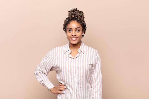 腰に手を当てて幸せそうに笑っている若いアフロ女性と自信を持って、前向きで、誇りに思って、フレンドリーな態度