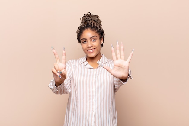 Young afro woman smiling and looking friendly, showing number seven or seventh with hand forward, counting down