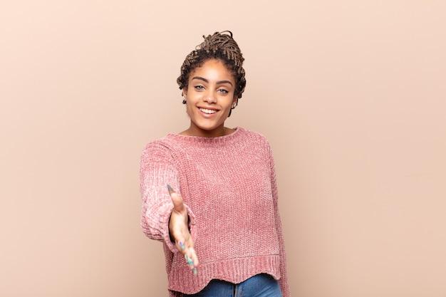 若いアフロ女性は笑顔で、幸せそうに見え、自信を持ってフレンドリーで、握手をして取引を成立させ、協力します