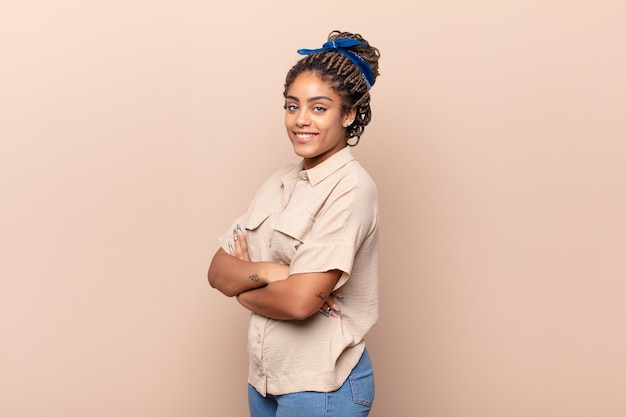 腕を組んで、幸せで、自信を持って、満足のいく表情、側面図で正面に微笑んでいる若いアフロ女性