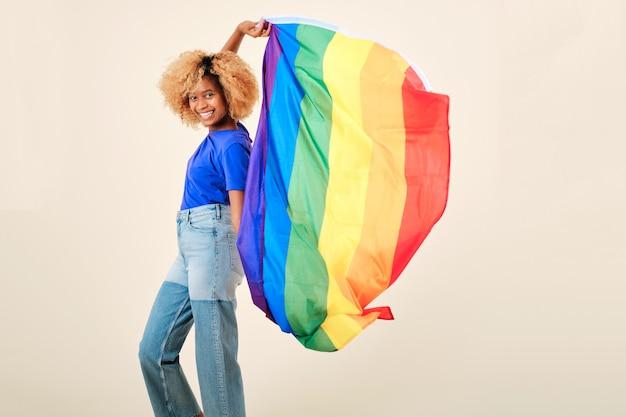 고립 된 배경에 게이 프라이드의 lgbtq 깃발을 들고 웃 고 젊은 아프리카 여성. lgbtq 커뮤니티 지원 개념입니다.
