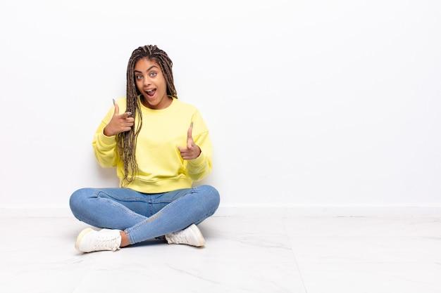 ポジティブで成功した、幸せな態度で笑顔の若いアフロ女性を指して、手で銃のサインを作る
