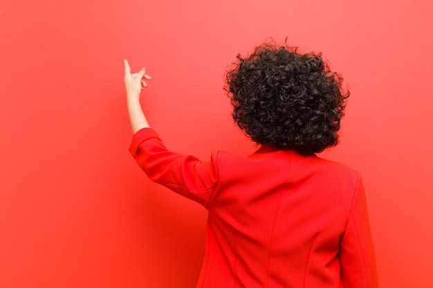 Young afro woman standing and pointing to object on copy space, rear view