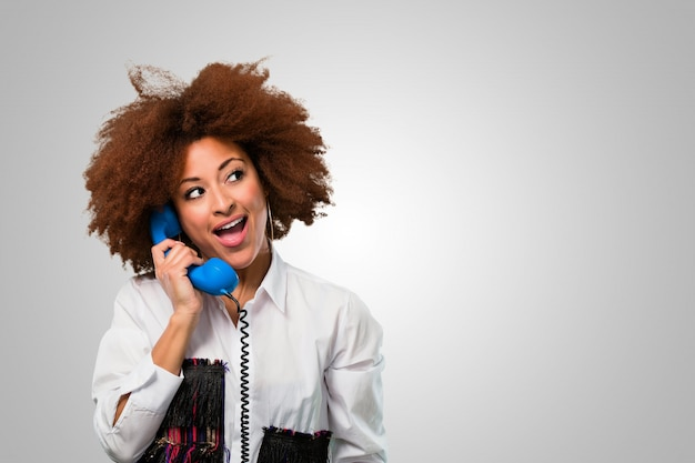 Young afro woman talking on a vintage telephone