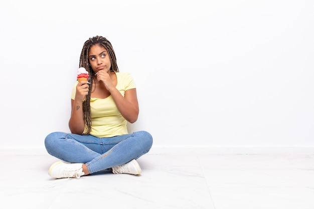 若いアフロの女性は、さまざまな選択肢を持って、疑わしくて混乱していると感じ、どの決定を下すか疑問に思っています。アイスクリームのコンセプト