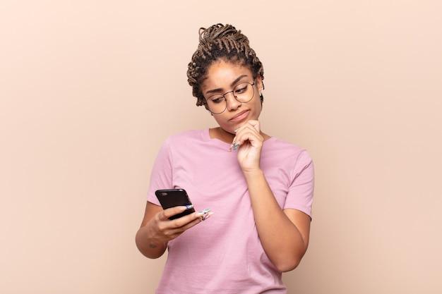 Молодая афро женщина думает, чувствует себя сомнительно и смущенно, с разными вариантами, задаваясь вопросом, какое решение принять. концепция смартфона
