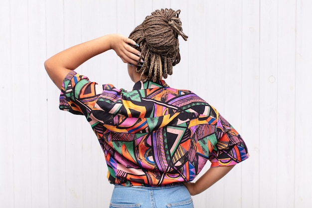考えたり疑ったり、頭を掻いたり、困惑したり混乱したりする若いアフロ女性、背面図または背面図