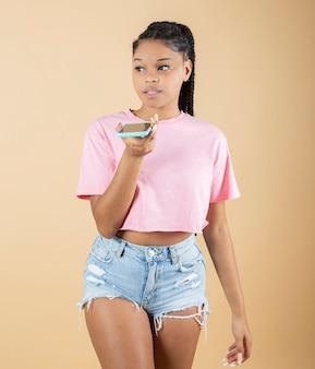 若いアフロ女性は黄色の背景に彼女の携帯電話を使用します
