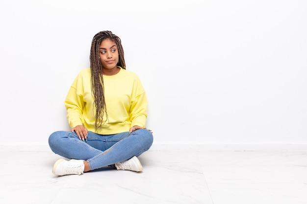 不思議に思って、幸せな考えやアイデアを考えて若いアフロ女性